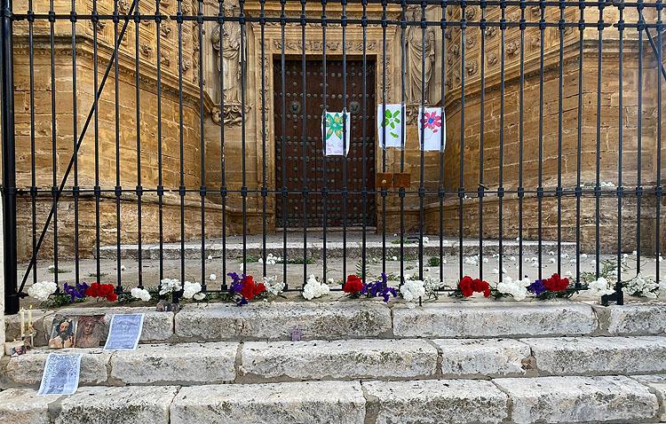 Flores y velas ante la parroquia de Santa María en honor a la hermandad de los Aceituneros