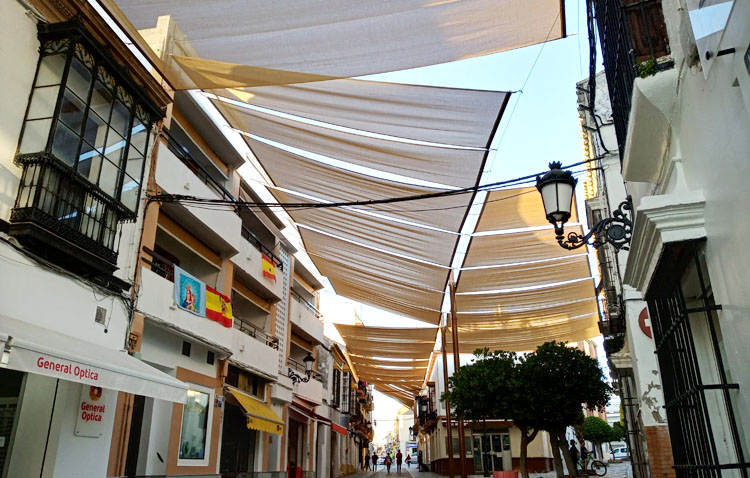 La utrerana calle Virgen de Consolación estrena sombra con el montaje de los nuevos toldos