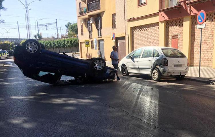 Un aparatoso accidente deja a un coche boca abajo tras colisionar con otros dos turismos en Utrera